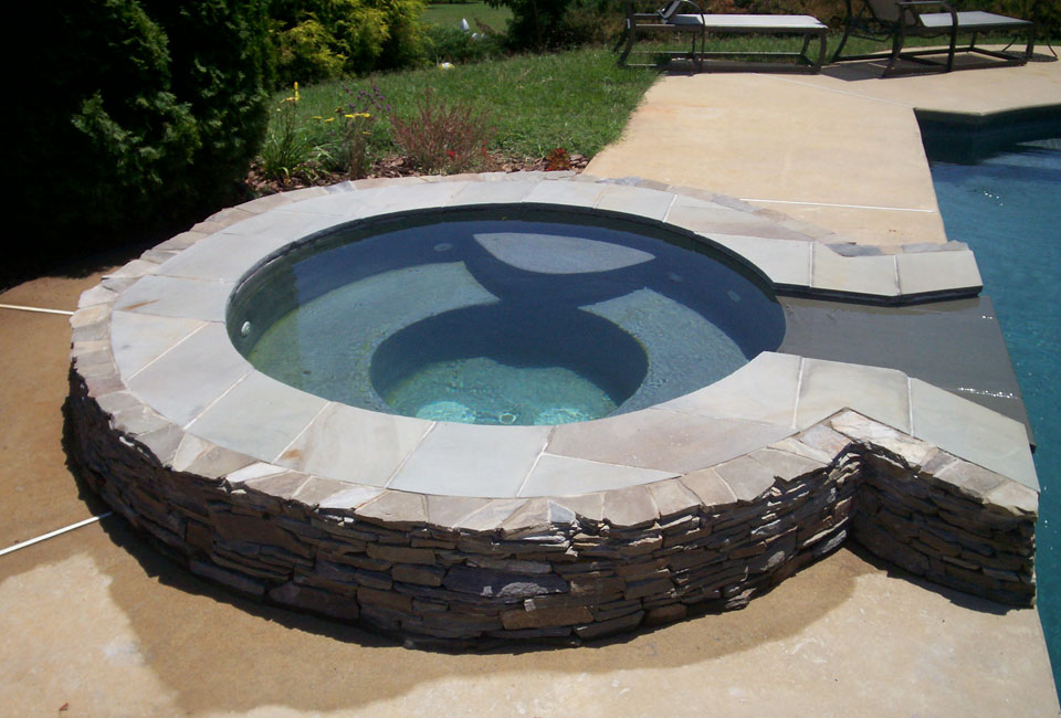 Poolside jacuzzi garden tub with mortared Pennsylvania stacked bluestone thin veneer enclosure with capstones for sitting