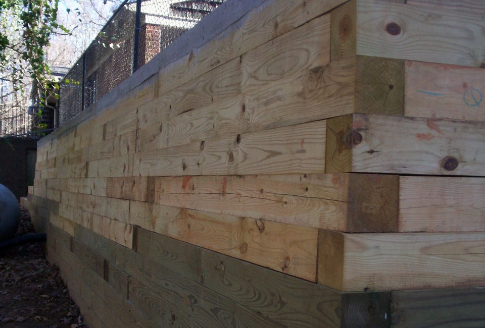 Pressure Treated Timber Retaining Wall w/ 'Deadman' Anchors built as Base for Poured Three Lane Driveway / Parking Area w/ Black Chain Link Fence