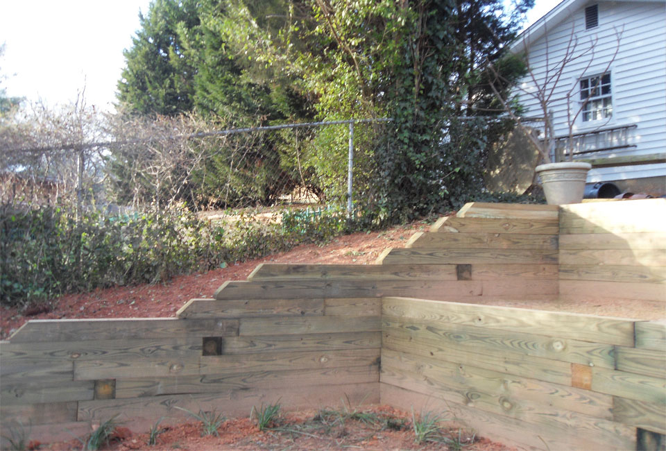 Multi-Level Tiered Timber Retaining Walls 'Stairing Down' rapidly on Upper Left Hillside of Back Yard featuring 'Deadman' Anchor System