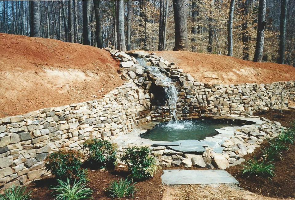 Large Scale Tennessee Fieldstone Retaining Wall w/ Steep Flowing Stream & Waterfall Into Pond w/ Recirculating Water  through BioFilter & skimmer filter inside pump house hidden by Carla Bluestone Flagstones