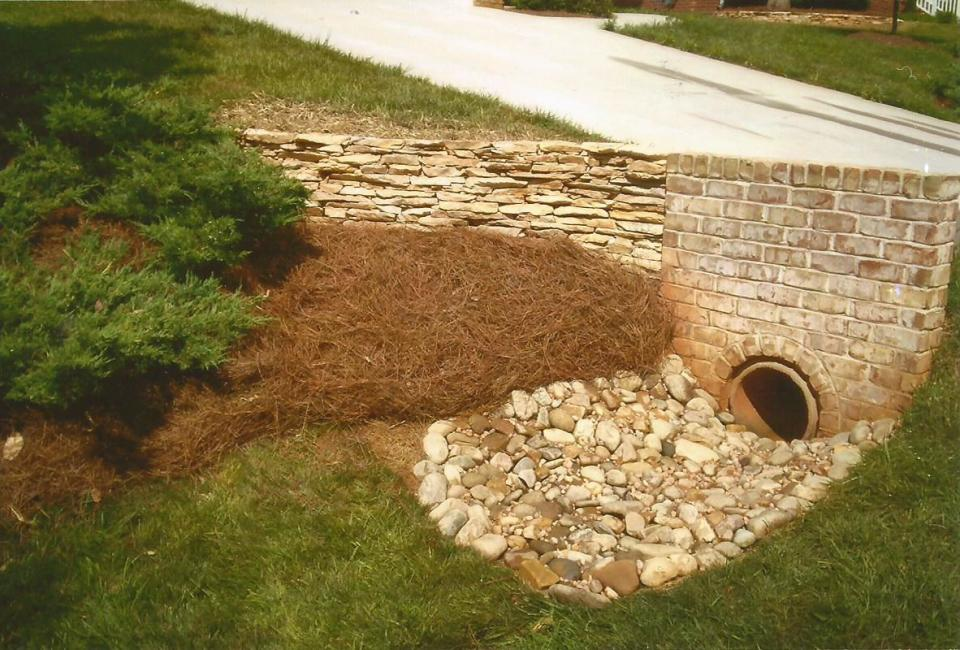 Tan Brick Housing Surrounding Driveway Drainage Piping Accentuated w/ ArkansasThin Veneer Retaining Wall & River Slicks at Base of Drainage Area Dry Creek Bed